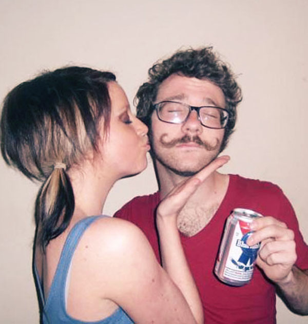 Man with glasses and a handle-bar mustache holding a pbr. A girl with pigtails is kissing his cheek.