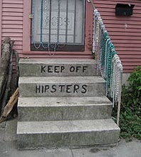"Front door of a house with a stoop with the words ""keep off hipsters"" written on the steps."