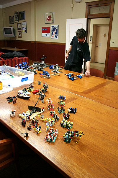 A man standing in front of a large table full of  action-related toys
