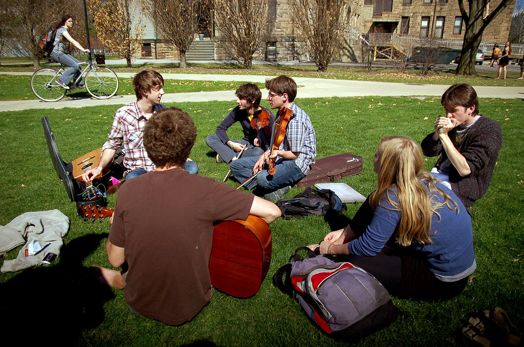 A group of Oberlin students sitting in Wilder bowl with instruments