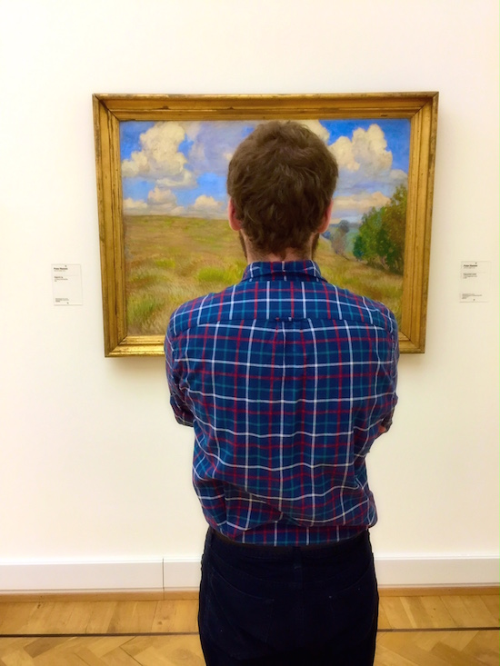 Someone looks at a painting in a museum
