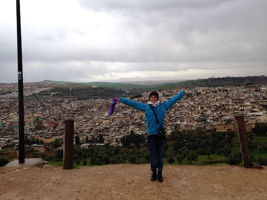 Georgia posing for a photo with her arms raised above her head in front of a large cityscape