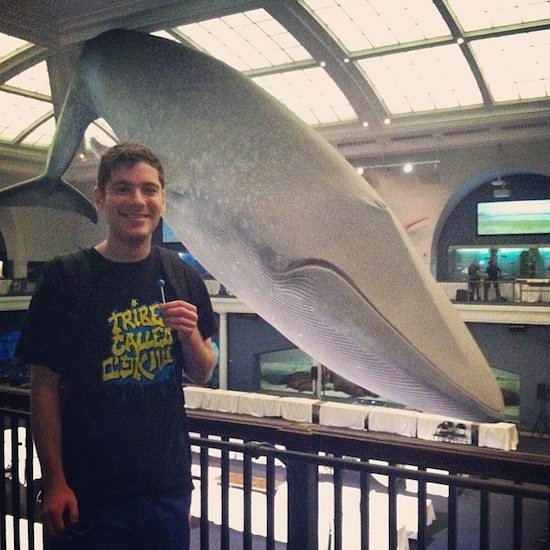 A student posing for a photo in front of a statue of a whale hanging from the ceiling.