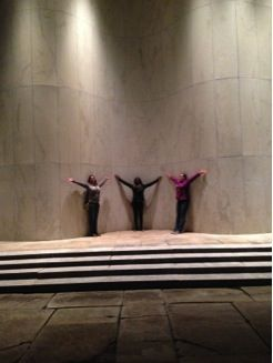 3 people at a distance, in front of a marble wall with arms outstretched