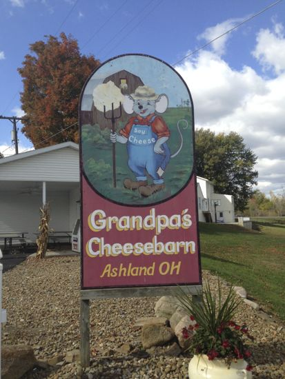 "A sign with a farmer mouse with the words: ""Grandpa's Cheesebarn, Ashland OH"""