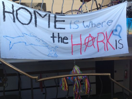 A handmade sign painted on a sheet proclaims 'Home is where the Hark is'