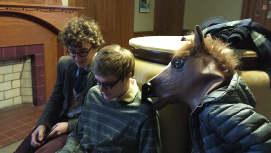 Two boys looking at a phone and another wearing a horse mask