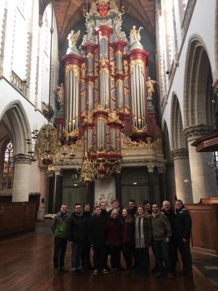 14 people by a large, ornate pipe organ
