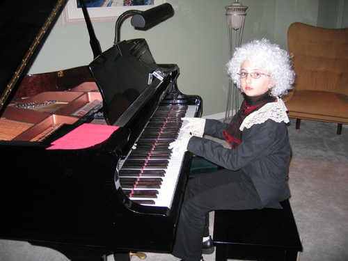 A young girl sits at a piano wearing a white wig