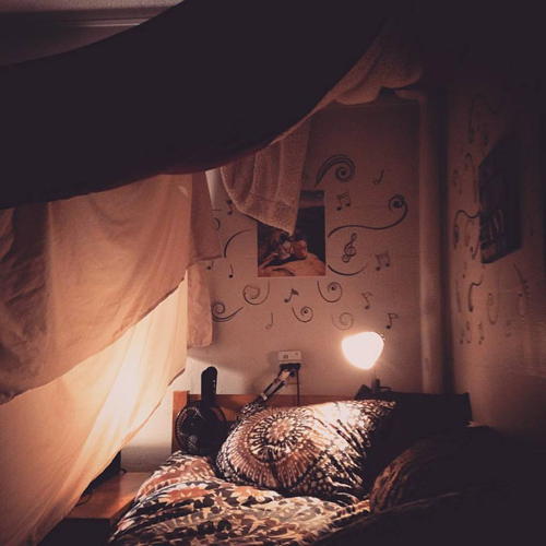 A cozy looking bed with dim lights