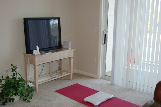 A yoga mat with a Wii Fit board in front of a TV