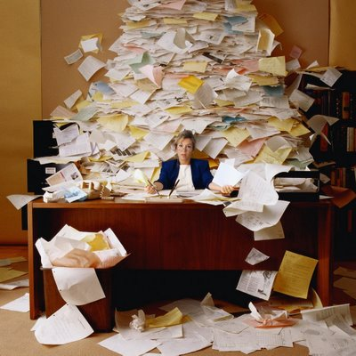 Stock photo of a woman at a desk surrounded by a mound of papers