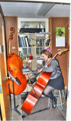 A student practicing the cello in a practice room