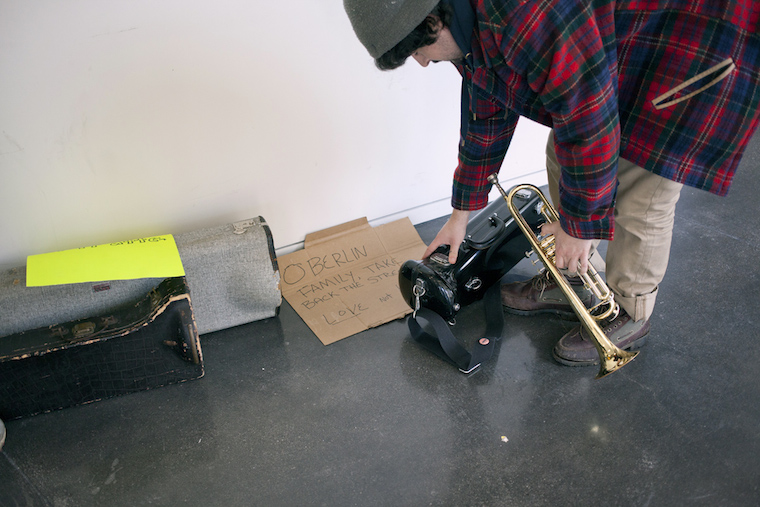 A student takes his trumpet out of the case