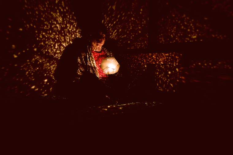 Student sitting in a dark room holding a light that emits light specks
