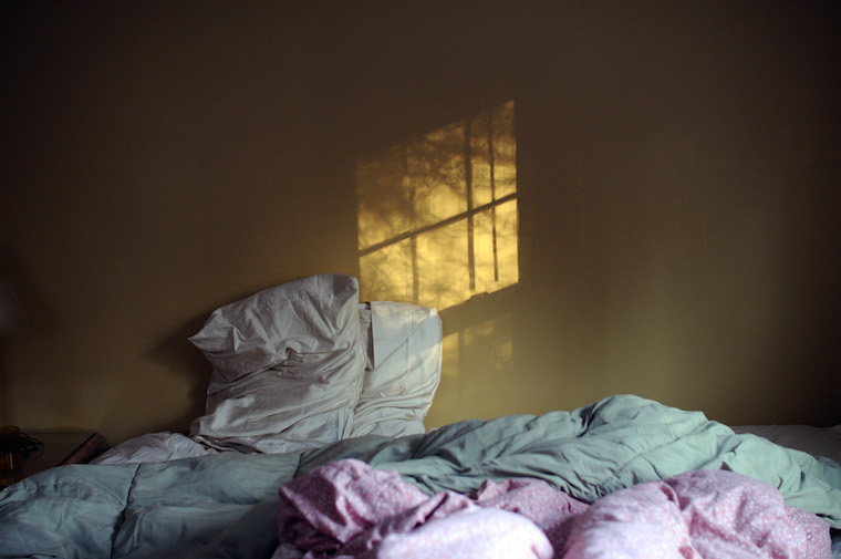 An unmade bed, the reflection of sun coming through a window onto a wall