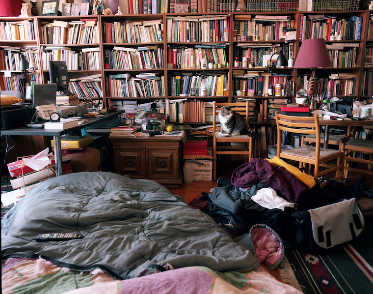 A room full of bookshelves, desks, a cat, a suitcase, and a make-shift bed on the floor