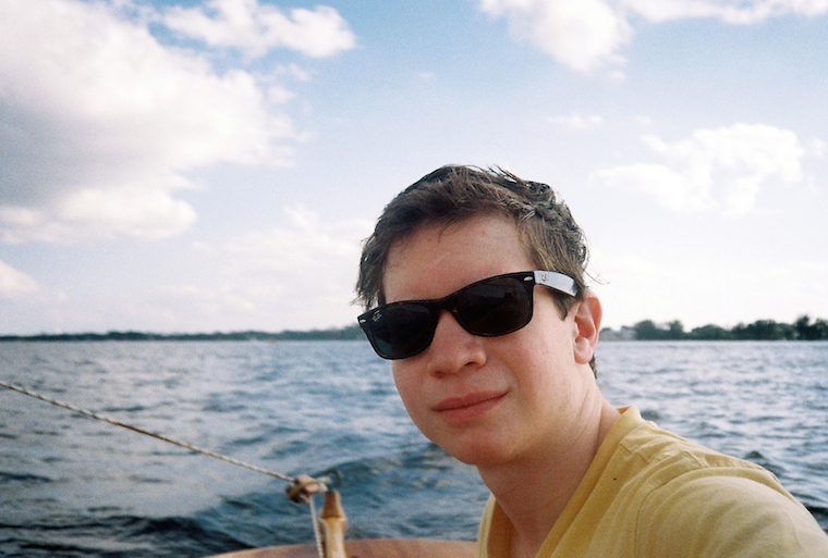 Student looks at the camera wearing sunglasses. He appears to be on a boat in the middle of a lake