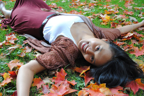 Student laying in a pile of leaves