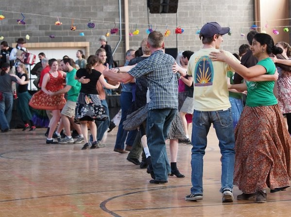 People of mixed ages contra-dancing in a gym.