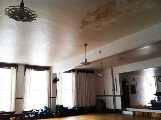 Large room with yoga mats. There is a stain on the ceiling.
