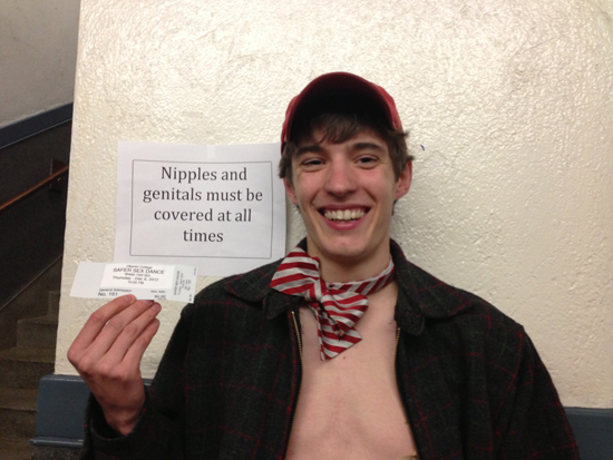 A guy in a bowtie with no shirt holds up an event ticket. The sign on the wall says, 'Nipples and genitals must be covered at all times.'