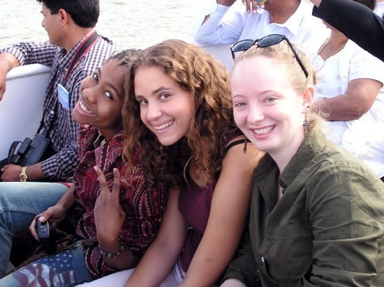 Three students smiling and posing for a photo on a boat