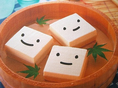 Blocks of tofu with smiley faces float in a bowl