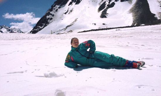 A girl wearing a turquoise snowsuit lounging in the snow