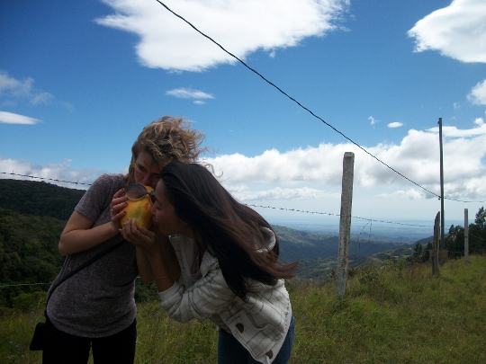 Two students eating a papaya in front of a mountain view