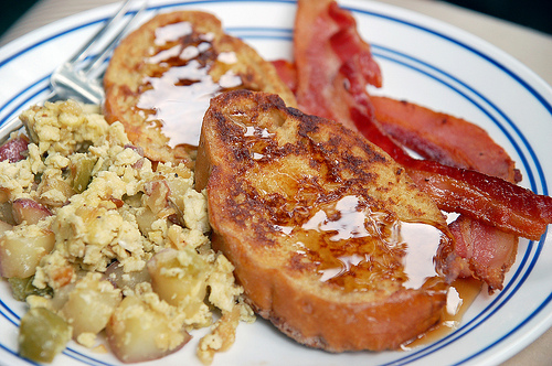 A plate of egg scramble, french toast, and bacon