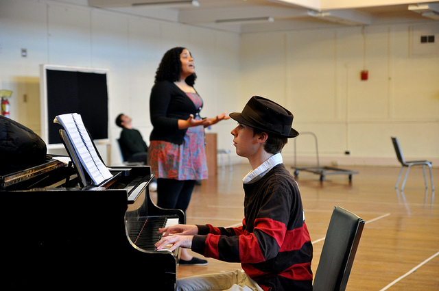 A student playing the piano and a student singing