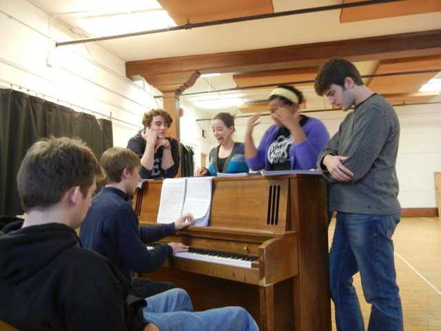 A group of students rehearsing around a piano
