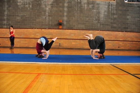 Two students stand on their heads on a mat