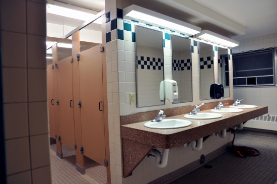Bathroom with 4 sinks and several stalls.