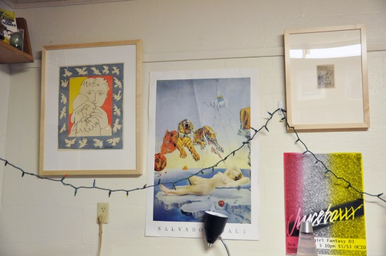 Two framed works of art amidst posters and a string of lights.
