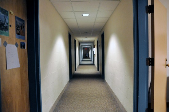 Looking down a long, straight corridor with evenly spaced doors on both sides.