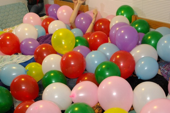 A student lays underneath a mass of balloons