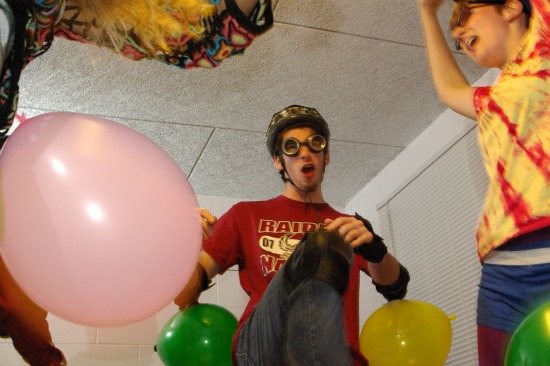 A student dances amid ballooons