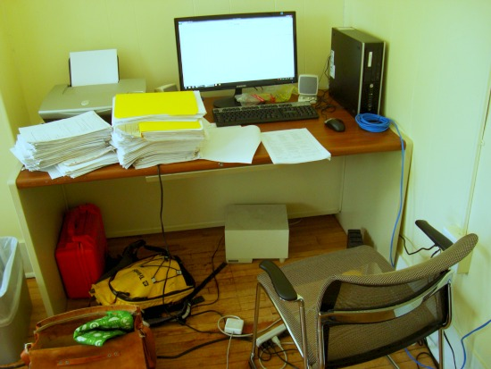 A desk with a computer and many stacks of paper