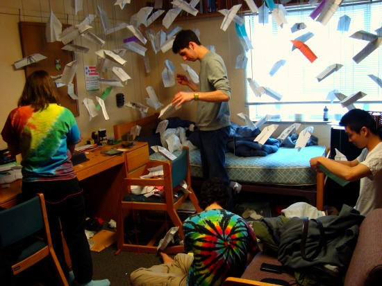 Many paper airplanes hang from the ceiling of a dorm room