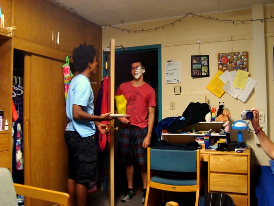 A student with whipped cream on his face and another holding a pie in a dorm room
