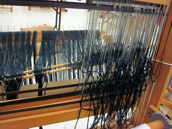 Threads being pulled through the heddles