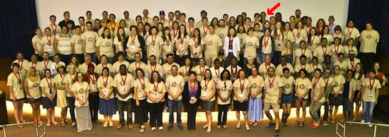A very large group of people posing for a photo. All have the same shirt with medals around their neck