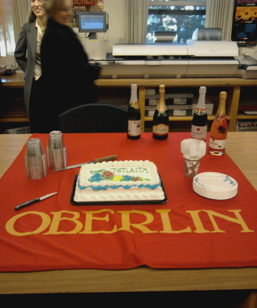 A cake and Champagne sits on an Oberlin cloth