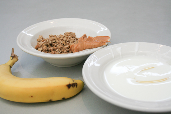 A bowl of yogurt, a bowl of granola and peanut butter, and a banana