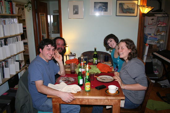 4 people enjoying a meal in a small apartment.