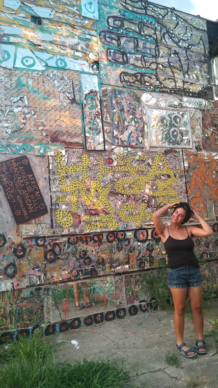 A woman poses in front of a decorated, outdoor wall