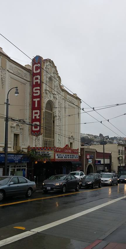 A view of The Castro theatre from across the street. The signage looks to be mid 20th century and cars line the street in busy traffic