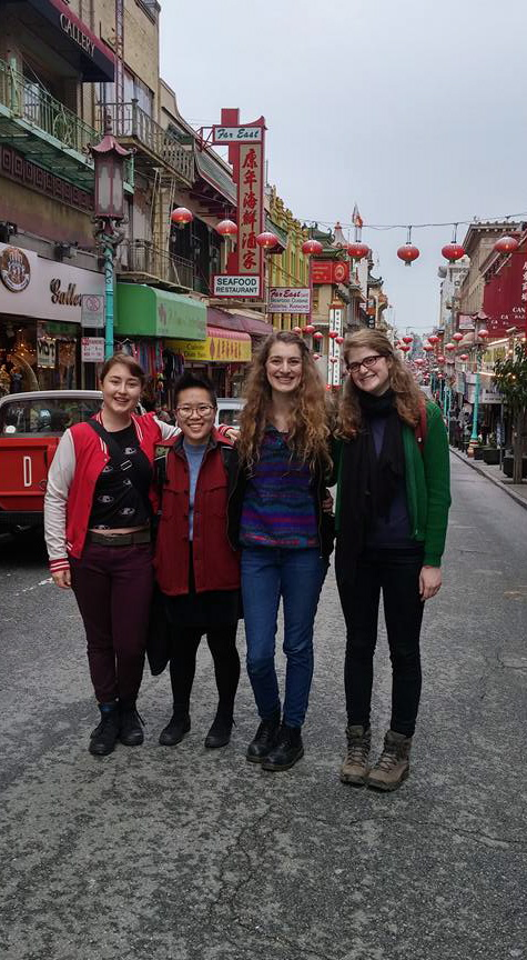 A group of four students posing for a picture in the streets of China town, surrounded by shops and hanging lanterns